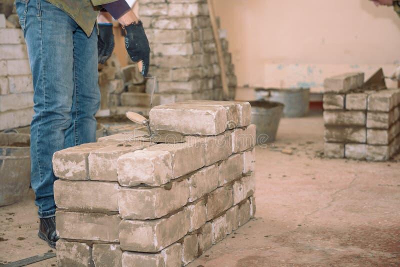 Construisez un mur des briques Les étudiants apprennent à étendre des briques Briques de lien de ciment Ciment tassé par spatule  images libres de droits