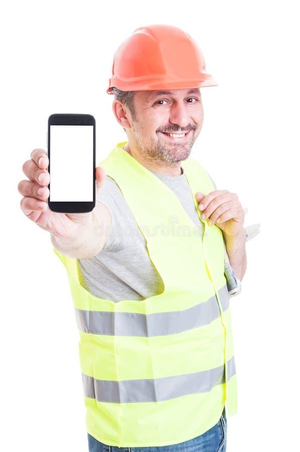 Construtor atrativo de sorriso que guarda o smartphone com tela vazia imagem de stock royalty free
