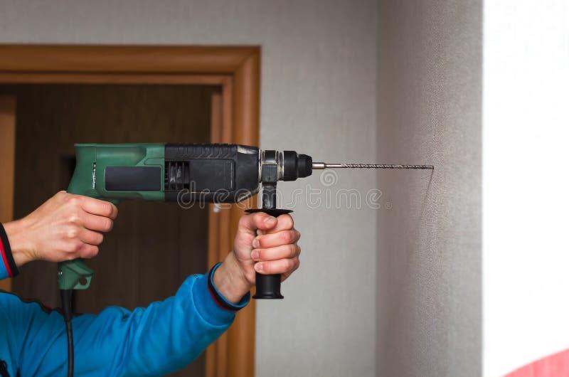Construtor com broca do perfurador foto de stock