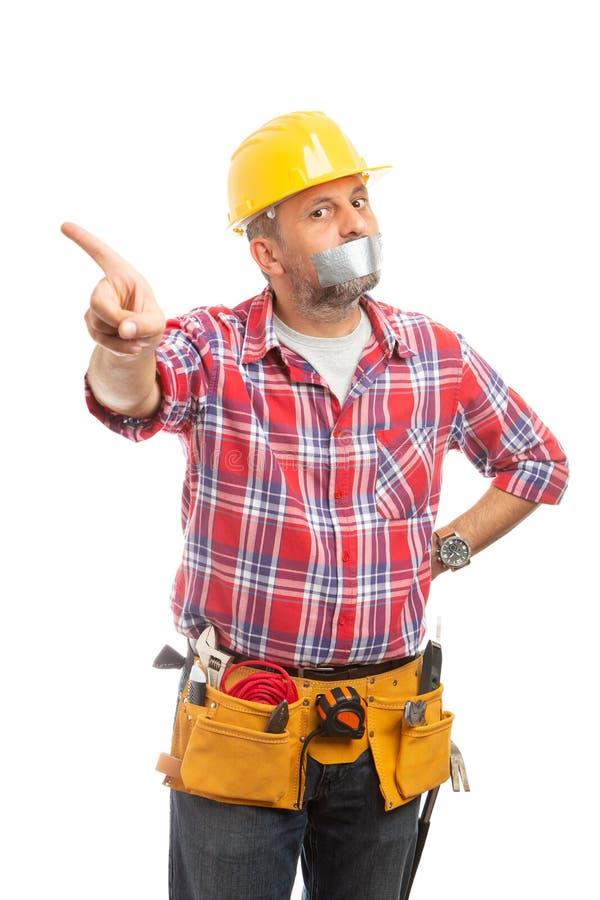 Construtor com a fita adesiva na boca que faz o gesto do movimento fotos de stock