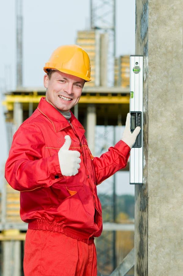 Construtor com nível digital foto de stock