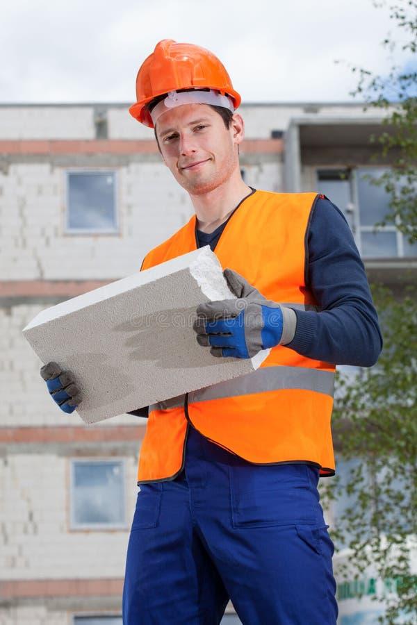 Construtor com um tijolo foto de stock royalty free