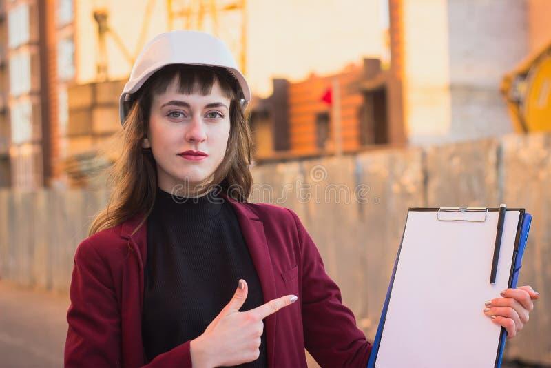 Construtor da mulher que guarda modelos, prancheta Menina de sorriso do arquiteto no capacete no fundo da construção imagens de stock