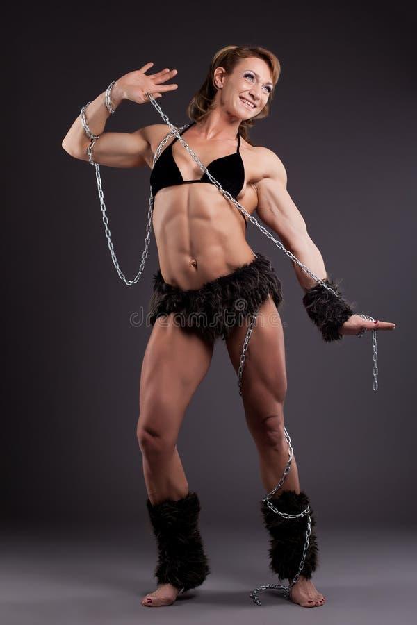 Construtor de corpo forte da mulher que levanta com corrente foto de stock