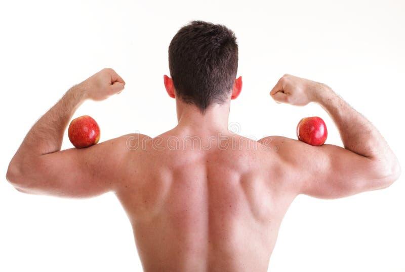 Construtor de corpo masculino 'sexy' atlético que guarda a maçã vermelha foto de stock royalty free