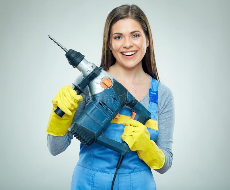 Construtor de sorriso da mulher que guarda o perfurador grande, broca imagens de stock royalty free