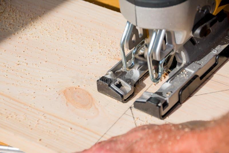 Construtor do carpinteiro do homem novo que trabalha com serra de vaivém e madeira elétricas Conceito do passatempo Acrônimo de D imagem de stock royalty free
