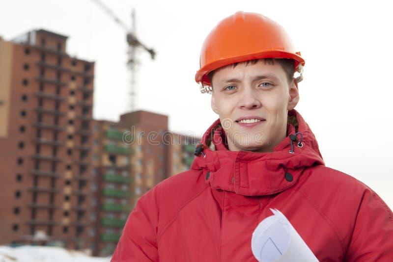 Construtor do coordenador no capacete no canteiro de obras foto de stock