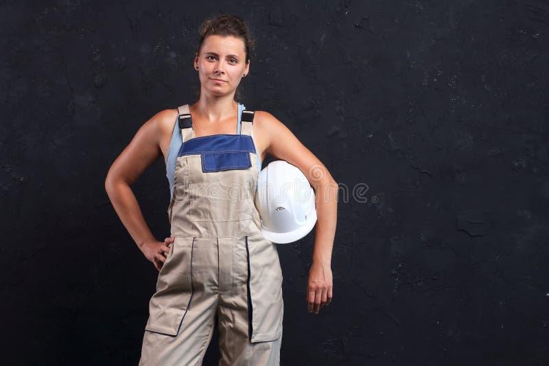 Construtor do trabalhador fêmea no capacete uniforme e branco Retrato do coordenador bonito da jovem mulher fotos de stock royalty free
