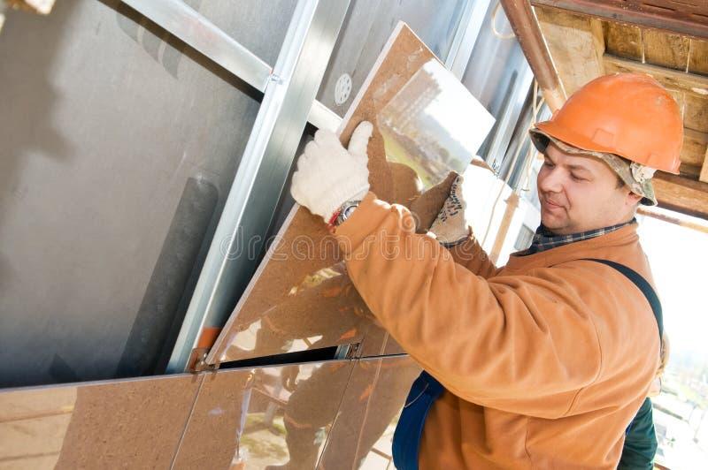 Construtor do trabalhador na telha da fachada imagens de stock royalty free