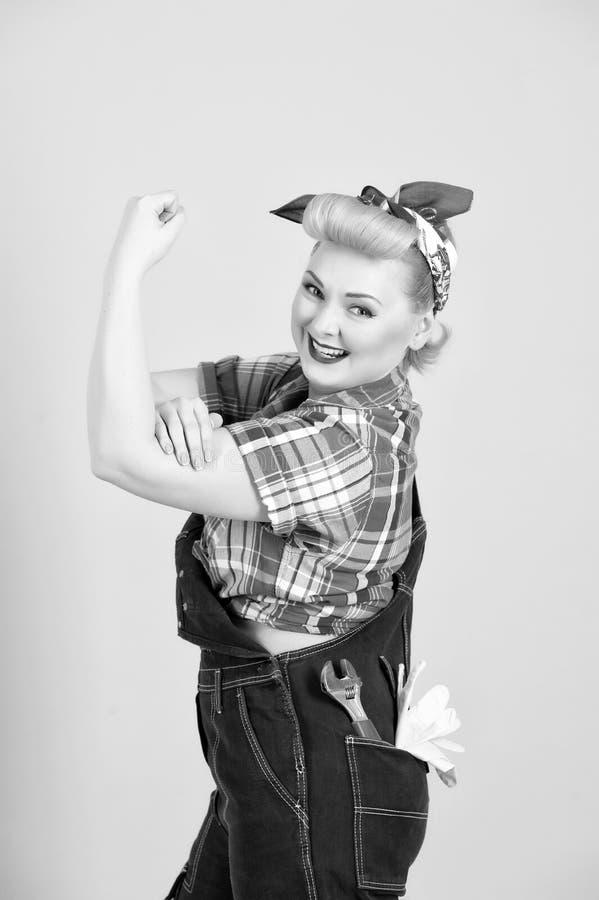 Construtor fêmea com o caspa principal vermelho nas calças de brim com chave no bolso fotos de stock