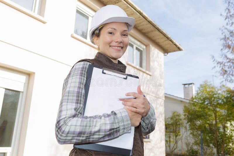 Construtor fêmea feliz em trabalhos do capacete de segurança no terreno de construção fotos de stock royalty free