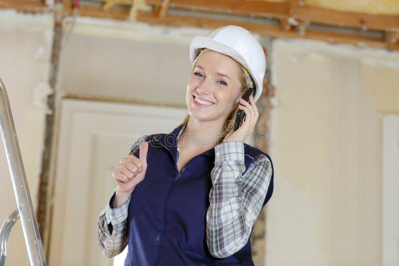 Construtor fêmea no telefone que faz os polegares acima do gesto foto de stock royalty free