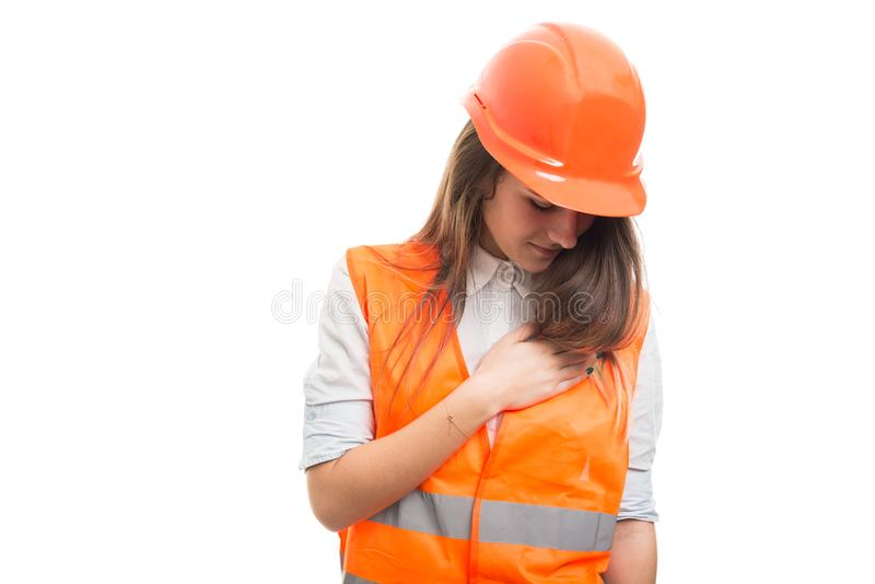 Construtor fêmea que arranja seu uniforme da proteção fotografia de stock
