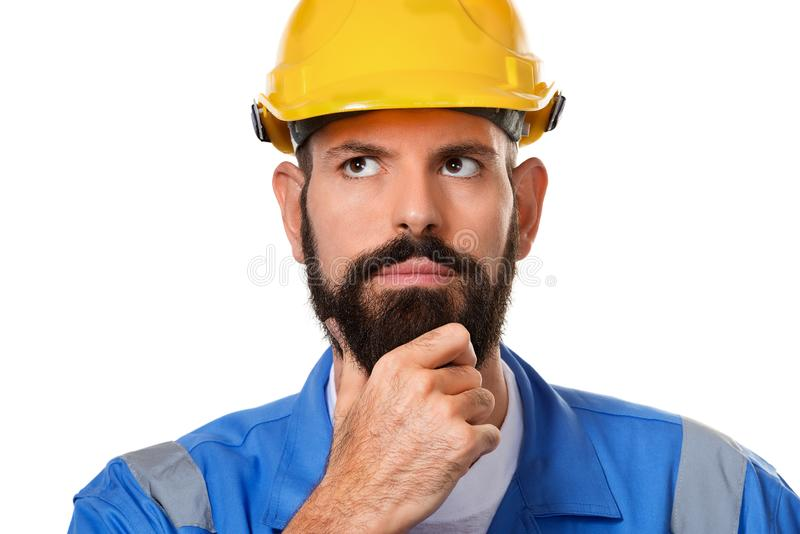 Construtor farpado pensativo no capacete de segurança, no contramestre ou no reparador no capacete Fim acima do construtor do arq fotografia de stock