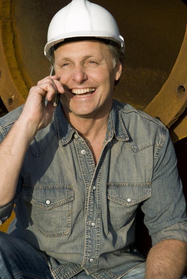 Construtor feliz no telemóvel fotografia de stock