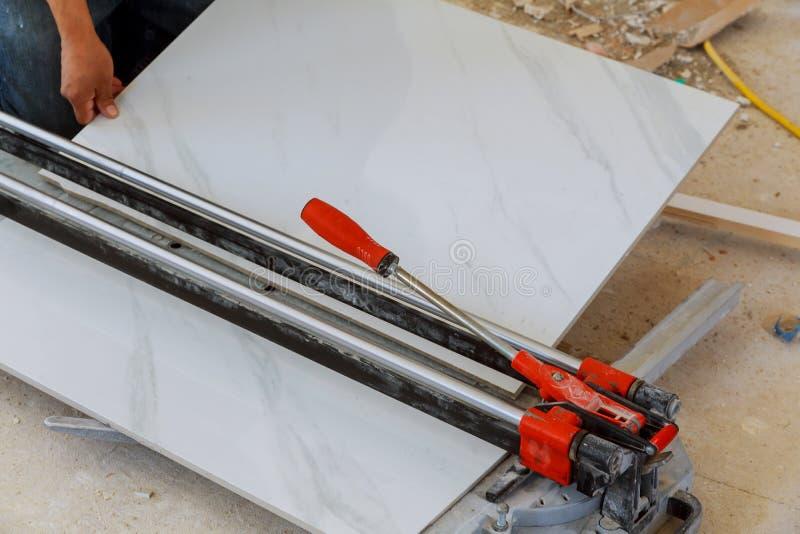 construtor industrial do tiler que trabalha com a telha de assoalho que corta o trabalho do reparo de equipamento imagem de stock royalty free