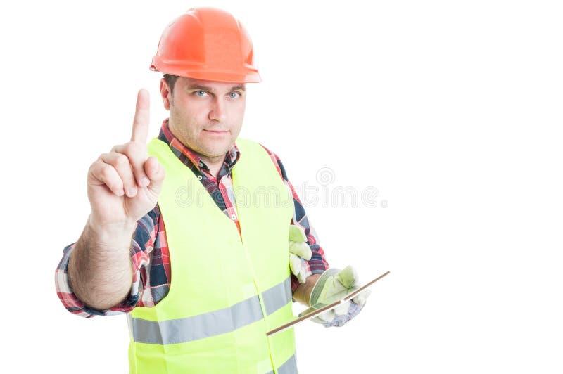 Construtor masculino com a tabuleta que faz um gesto de espera imagens de stock