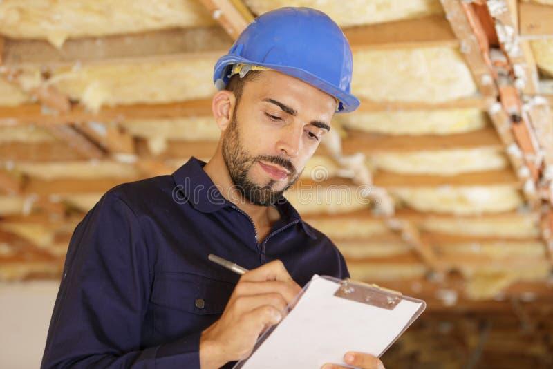 Construtor masculino ou trabalhador manual na escrita do capacete na prancheta fotografia de stock