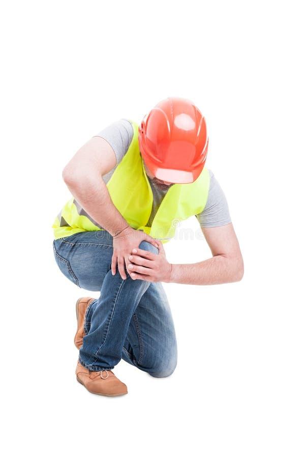 Construtor masculino que ajoelha-se e que sofre da dor do joelho fotografia de stock