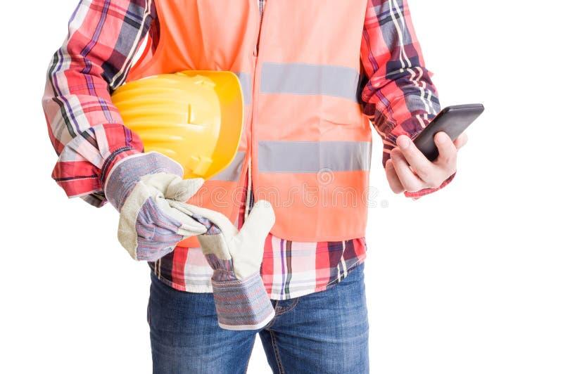 Construtor moderno que verifica o smartphone foto de stock