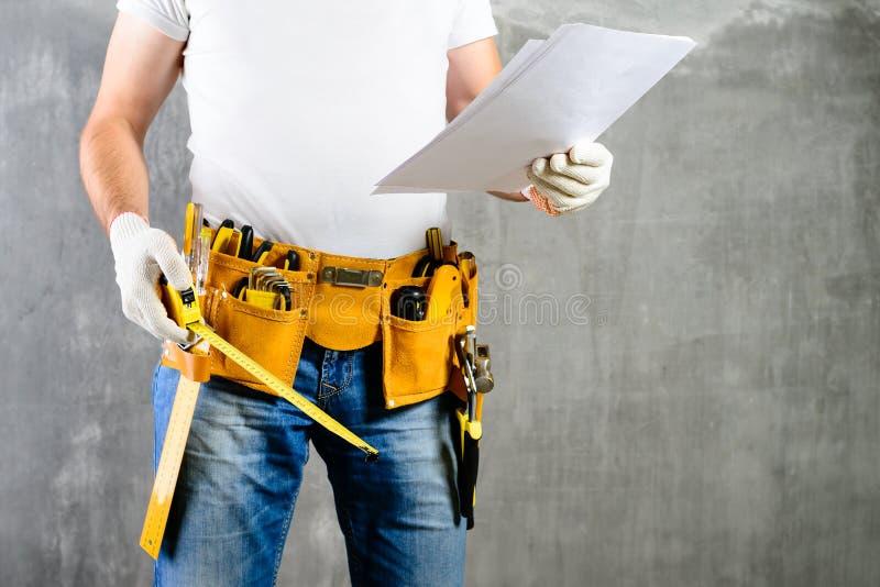 Construtor não identificado que está nas luvas brancas com uma correia w da ferramenta imagem de stock
