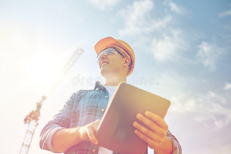 Construtor no capacete de segurança com o PC da tabuleta na construção imagem de stock