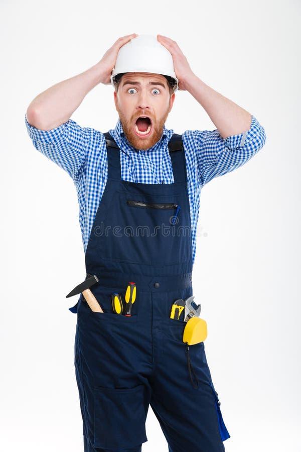Construtor no capacete que staning com a boca aberta imagens de stock