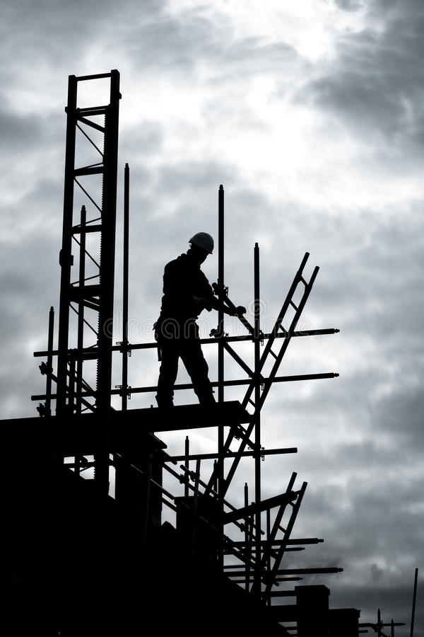Construtor no local de edifício do andaime imagens de stock royalty free