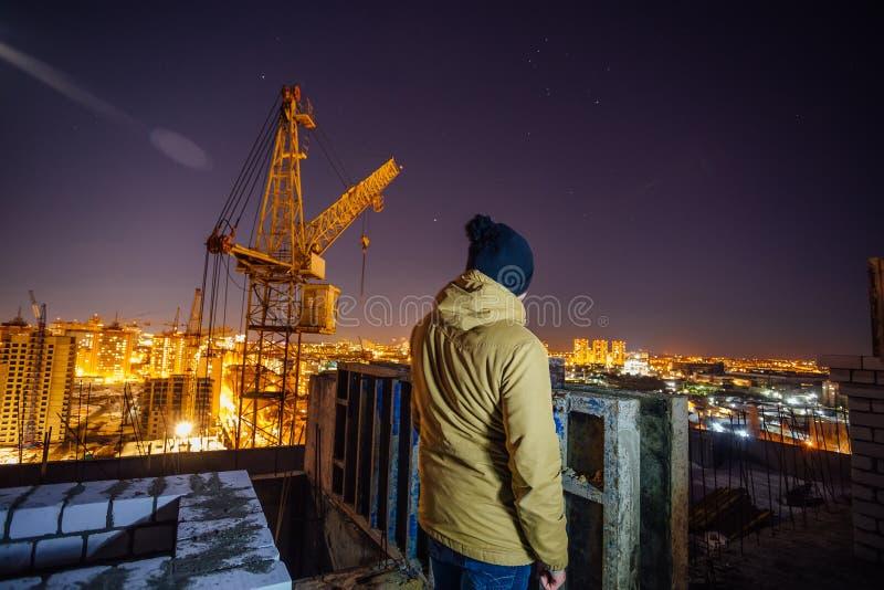 Construtor no telhado da construção moderna inacabado no fundo do canteiro do guindaste e das obras, opinião da noite fotografia de stock