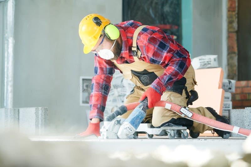 Construtor no trabalho cortando o assoalho concreto para cabografar pela máquina de corte do diamante fotos de stock royalty free