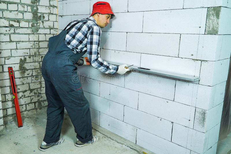 Construtor no trabalho para vestir a verificação da regularidade da parede do bloco com a régua da construção fotografia de stock royalty free