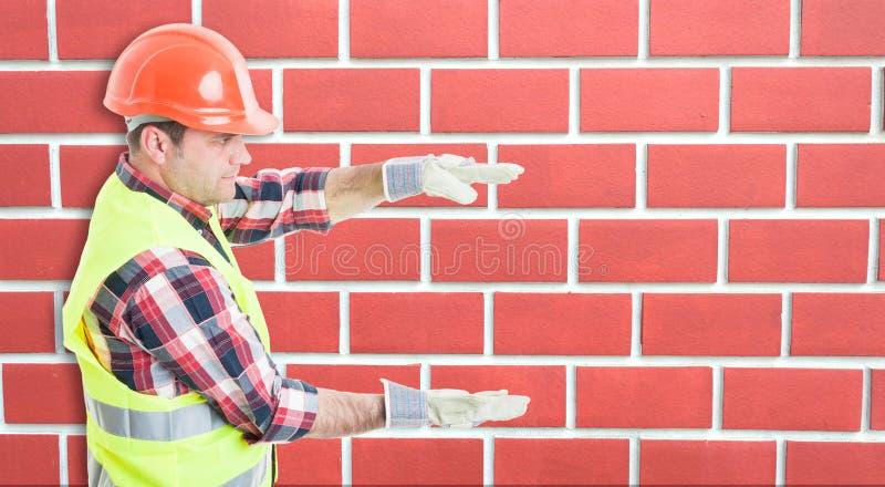 Construtor novo com o algo grande entre as mãos foto de stock