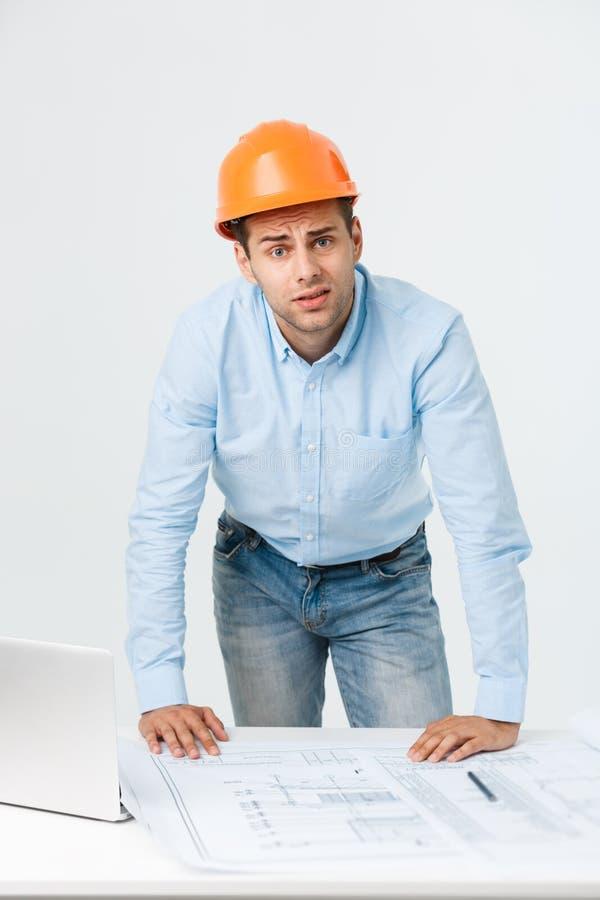Construtor novo forçado que tem a dor de cabeça ou a enxaqueca que olham esgotada e preocupada isolado no fundo branco com fotos de stock royalty free