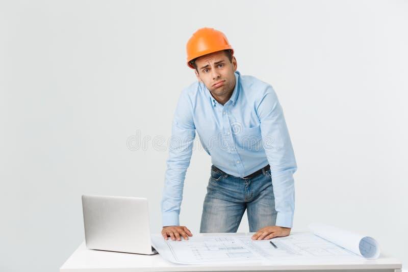 Construtor novo forçado que tem a dor de cabeça ou a enxaqueca que olham esgotada e preocupada no fundo branco com foto de stock royalty free