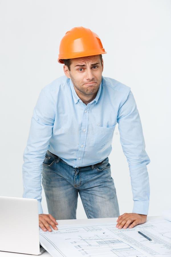 Construtor novo forçado que tem a dor de cabeça ou a enxaqueca que olham esgotada e preocupada no fundo branco com fotos de stock