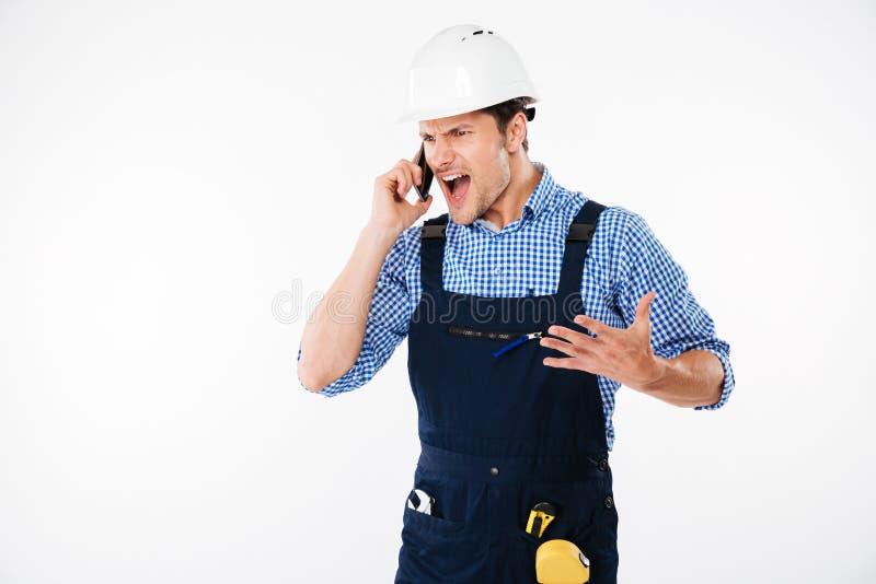 Construtor novo gritando irritado que fala no telefone imagens de stock royalty free