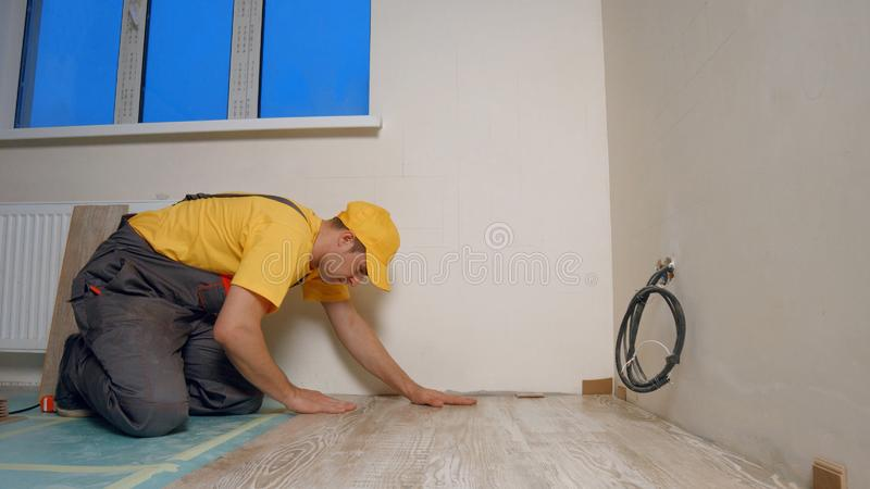 Construtor novo que coloca o parquet no apartamento novo imagens de stock royalty free