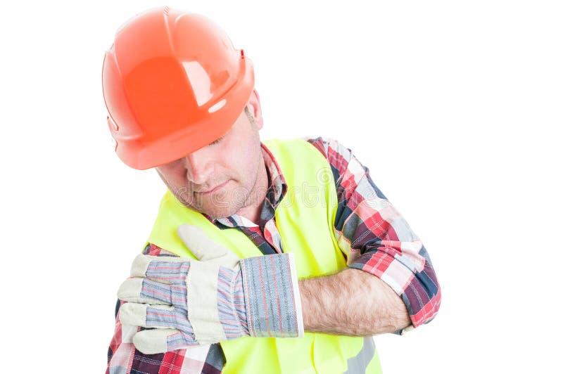 Construtor novo que fere o ombro imagem de stock