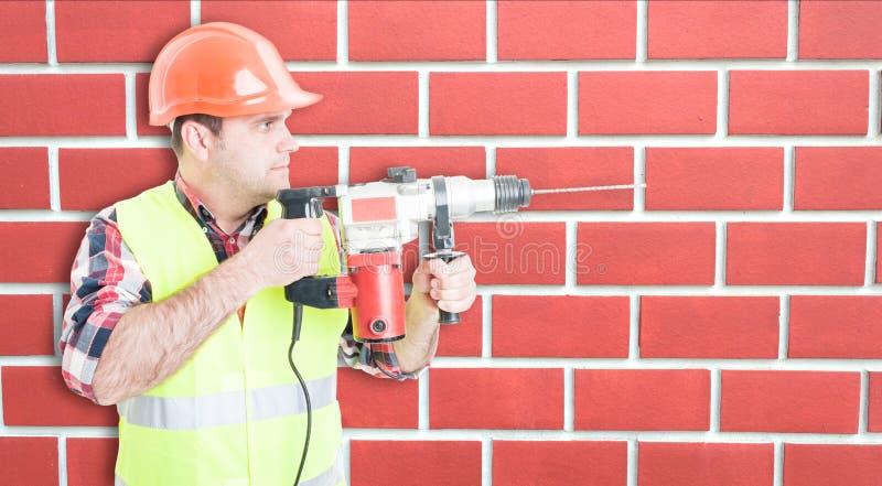 Construtor ocupado que repara algo com ferramenta da broca fotografia de stock