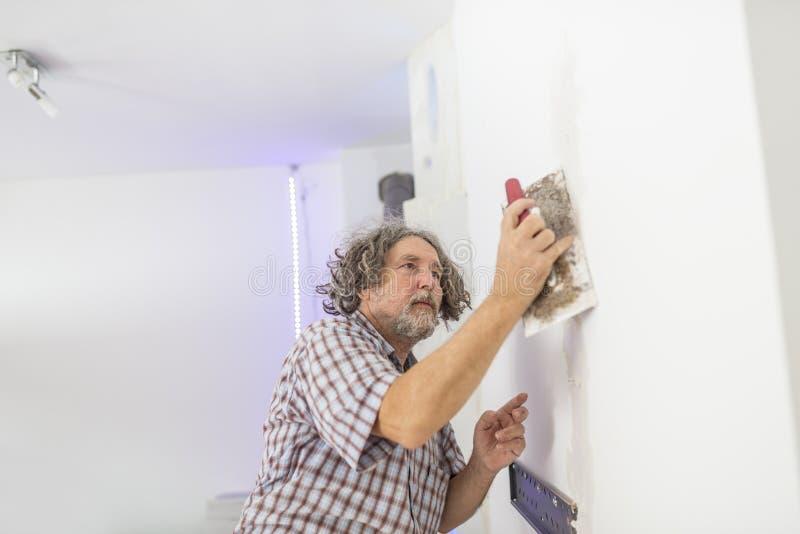 Construtor ou proprietário masculino de meia idade que emplastram um PR branco da parede fotos de stock royalty free