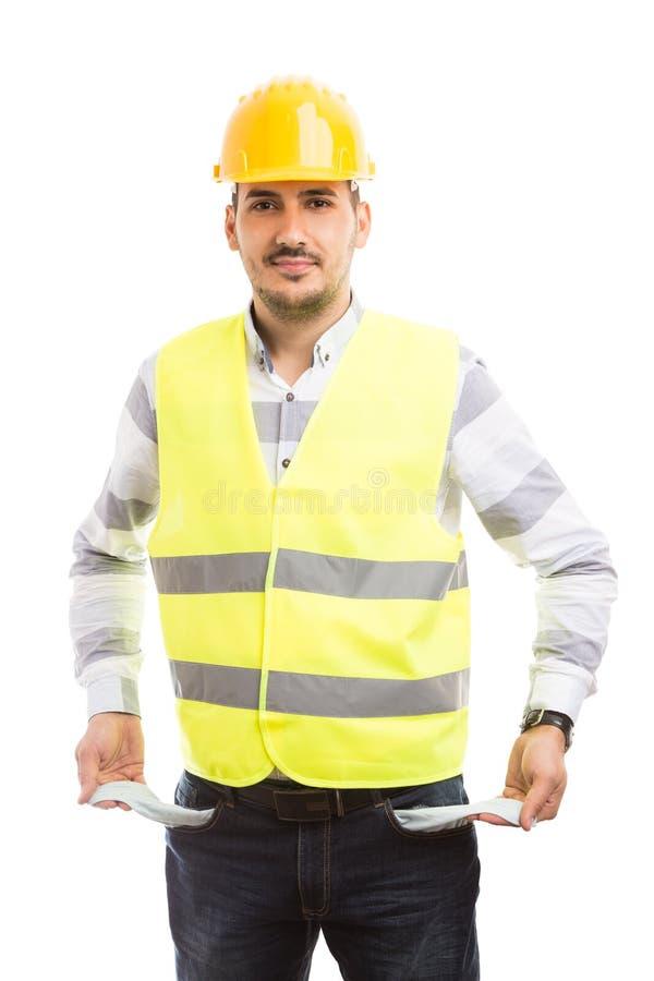 Construtor ou construtor que mostram bolsos de calças vazios fotografia de stock