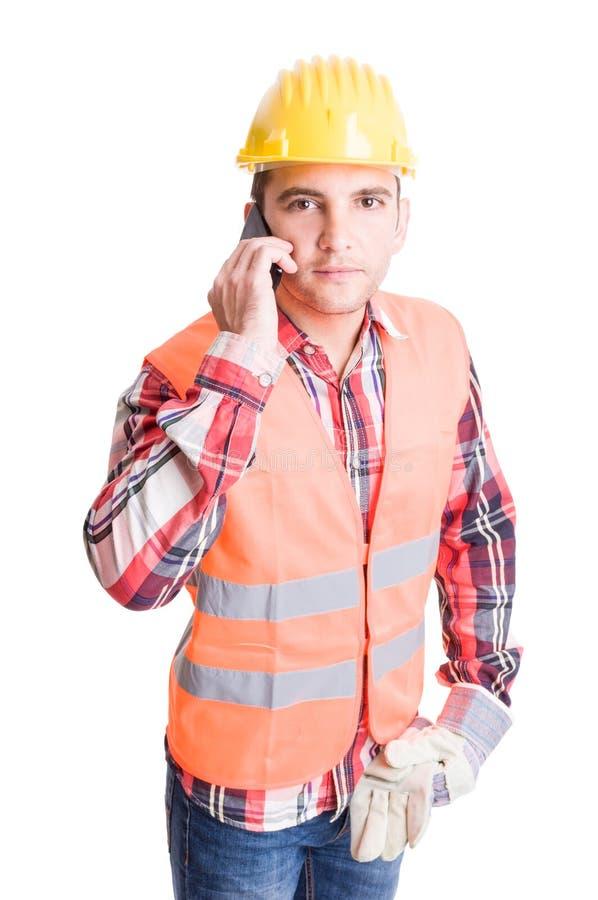 Construtor profissional e moderno que usa o smartphone fotografia de stock
