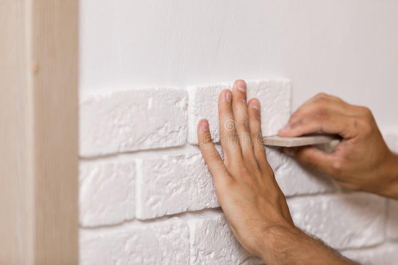 Construtor profissional que cola a telha decorativa na parede imagem de stock