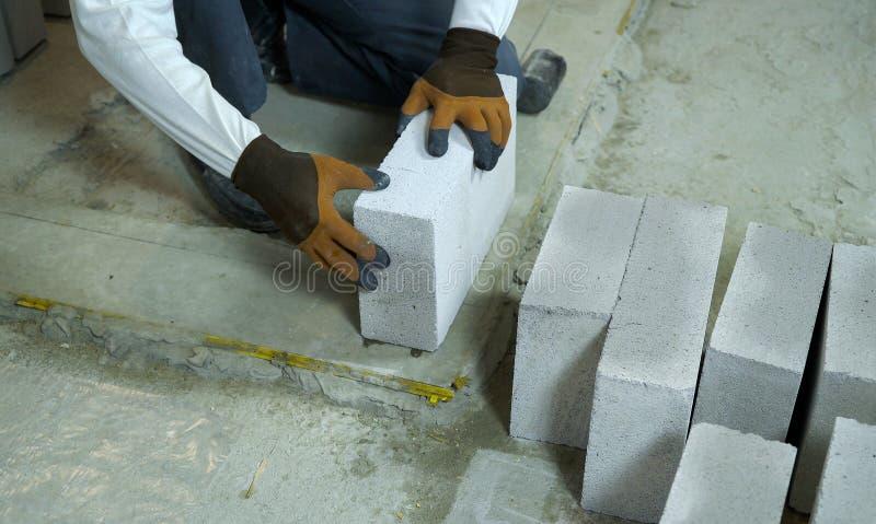 Construtor que coloca o bloco de cimento ventilado na fundação do cimento fotografia de stock
