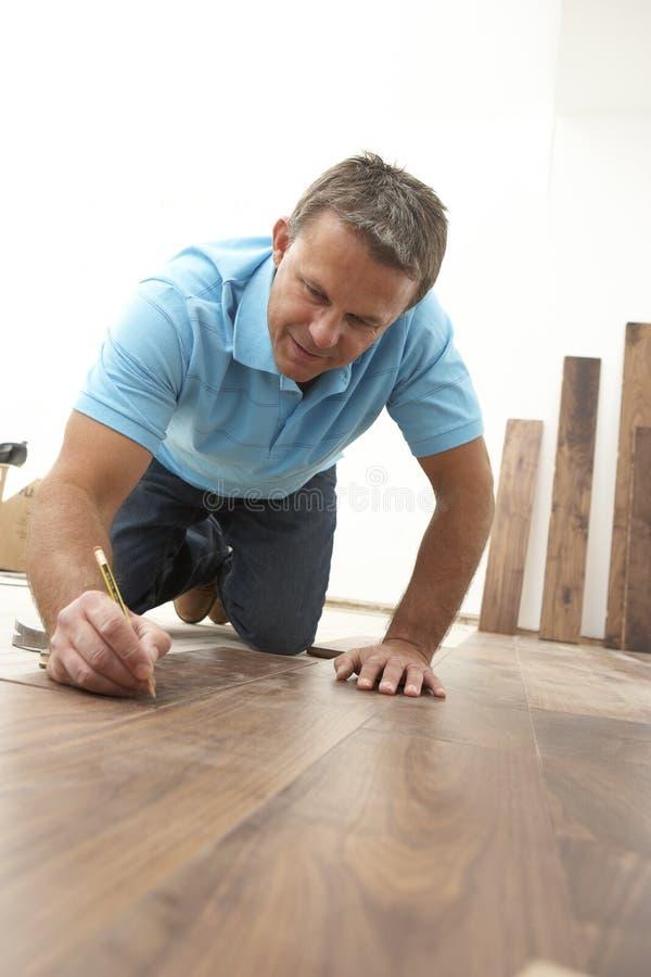 Construtor que coloca o revestimento de madeira imagem de stock