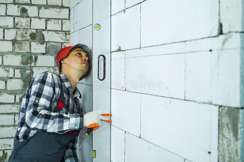 Construtor que pressiona o nível de bolha para obstruir a parede que verifica verticalmente sua qualidade fotografia de stock