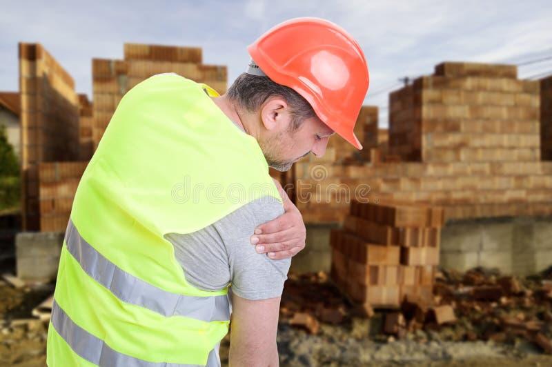 Construtor que sofre da dor do ombro imagens de stock