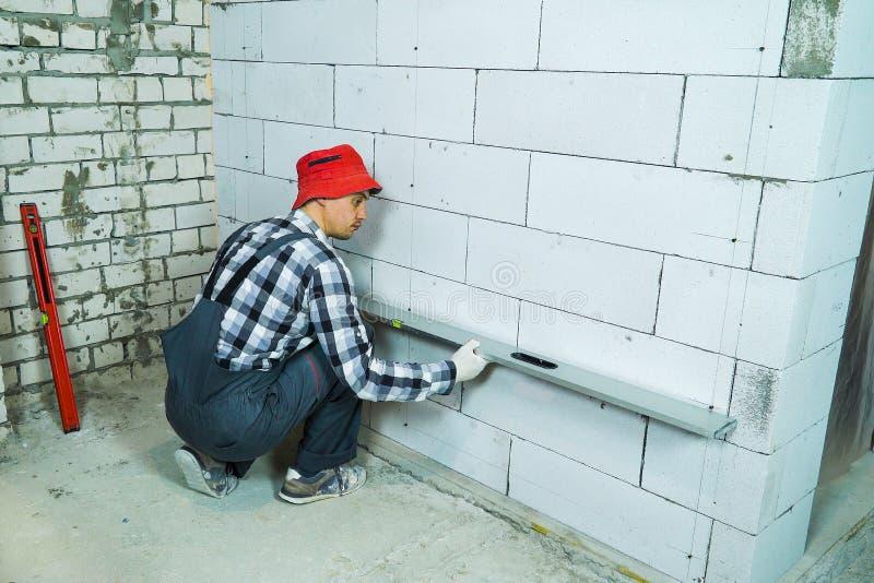Construtor que verifica a qualidade da parede ventilada do bloco de cimento com a r?gua da constru??o imagens de stock royalty free