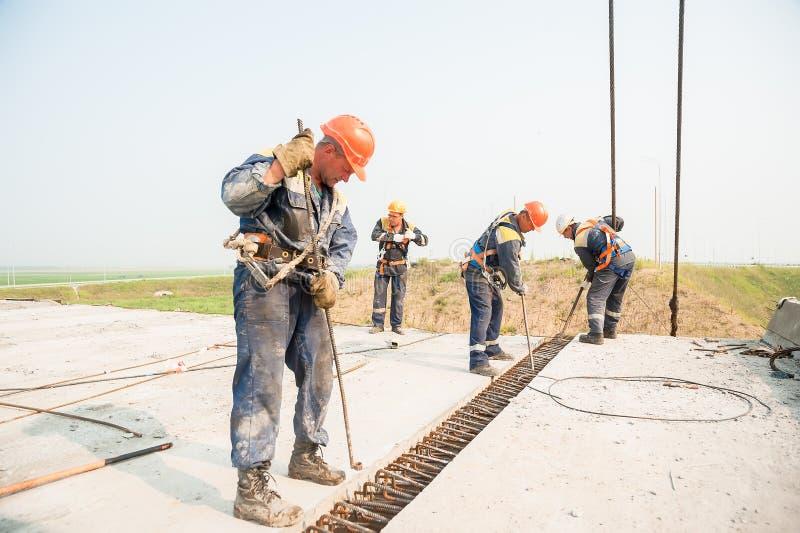 Construtores com a barra do corvo do metal que instala o concreto imagem de stock royalty free